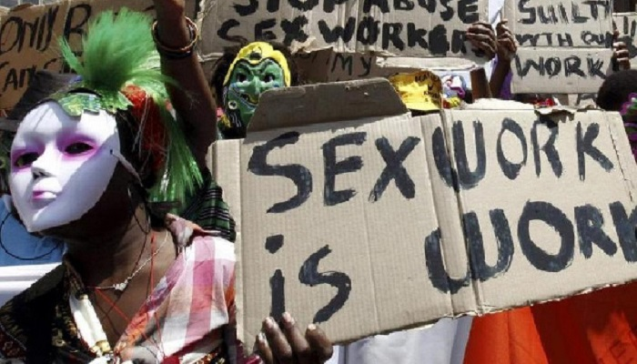 Sex workers holding a placard with the inscription ' Sex work is work'