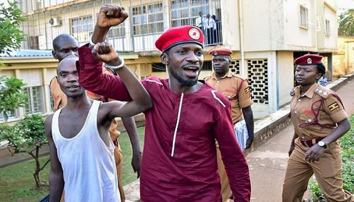 Bobi Wine walks handcuffed together with another prisoner after his arrest in April