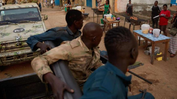 South Sudan National Police Service officers sit on the back of a pickup truck while they patrol